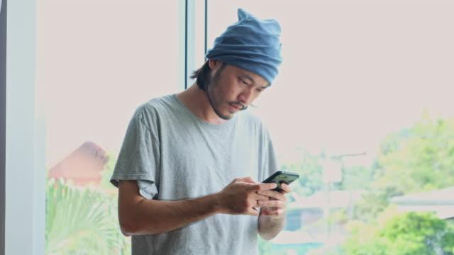 vidéos et rushes de lutte asiatique de jeune homme tout en utilisant le téléphone intelligent à la maison - déception