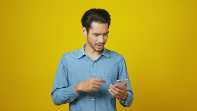 junge asiatische mann kämpfen mit handy, asia männlich mit smartphone, während über gelben hintergrund im studio, menschen und kommunikationstechnologie stehen - frustration stock-videos und b-roll-filmmaterial