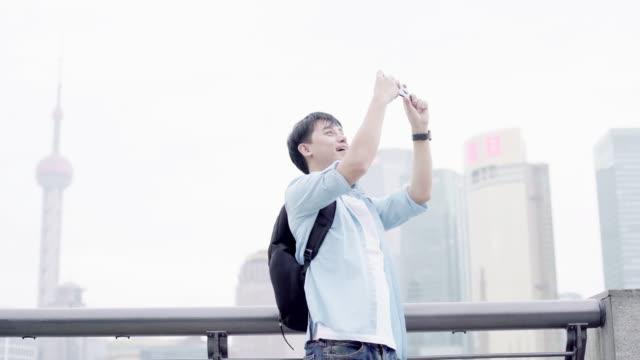 junge asiatische mann fotografieren mit handy in shanghai - fotohandy stock-videos und b-roll-filmmaterial