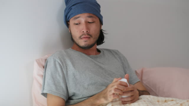 young asian man taking pill while lying on bed, people healthcare and medical - painkiller stock videos & royalty-free footage