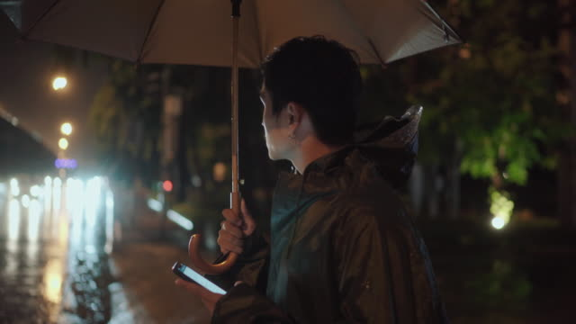 young asian man taking taxi or uber late in the night. he is in the street holding an umbrella in a cold rainy night. - after work stock videos & royalty-free footage