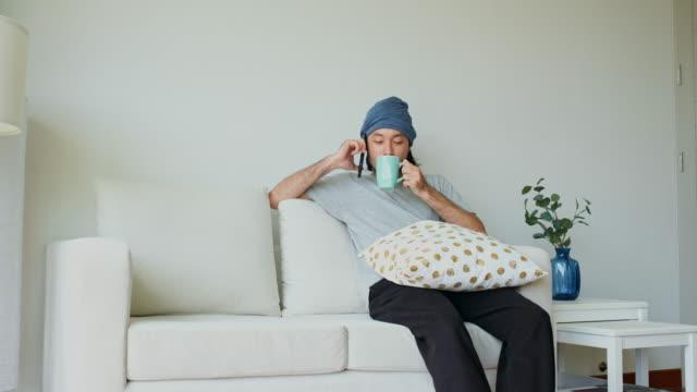 朝、自宅のリビングルームで電話を話し、コーヒーを飲むアジアの若い男性 - 30代点の映像素材/bロール
