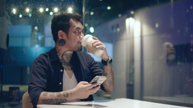 junger asiatischer mann sms mit smartphone am café-tisch - freischaffender stock-videos und b-roll-filmmaterial