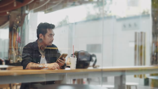young asian man texting with smartphone at cafe table - one young man only stock videos & royalty-free footage