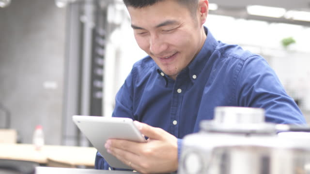 young asian man using digital tablet