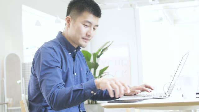 vídeos y material grabado en eventos de stock de hombre joven asiático utilizando el ordenador portátil - mirar hacia abajo