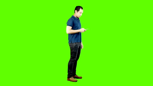 young asian man using mobile phone on green background. - standing stock videos & royalty-free footage