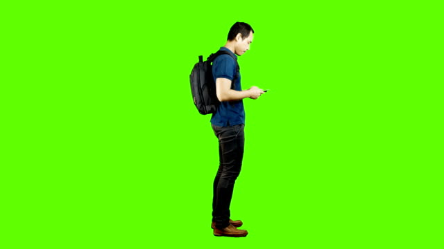 young asian man using mobile phone on green background. - 站姿 個影片檔及 b 捲影像