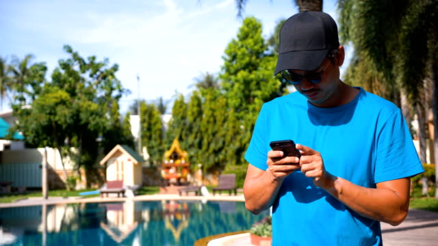 Young Asian man using mobile phone touchscreen at swimming Pool.