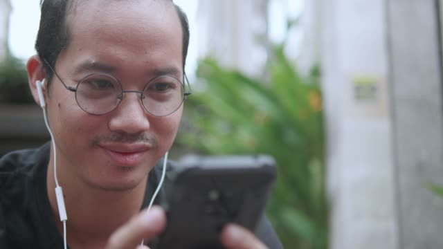 Young Asian man using mobile phone touchscreen. working on the phone. Concept: new business, travel, communication.