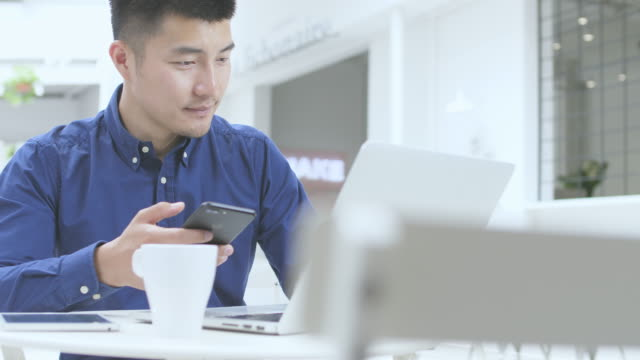 young asian man using mobile phone