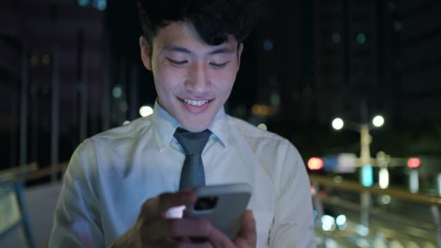 vídeos y material grabado en eventos de stock de joven asiático usando el teléfono en la pasarela por la noche - 25 29 años