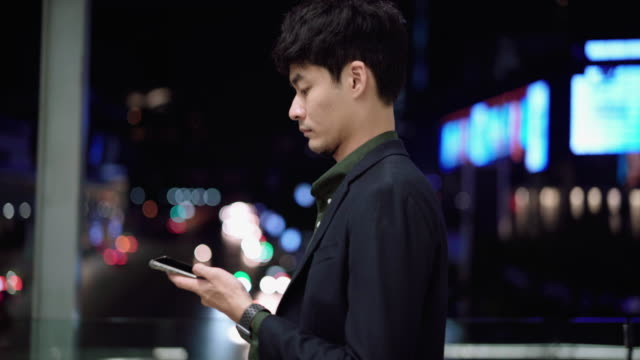 young asian man using smart phone at night street - phone message stock videos & royalty-free footage