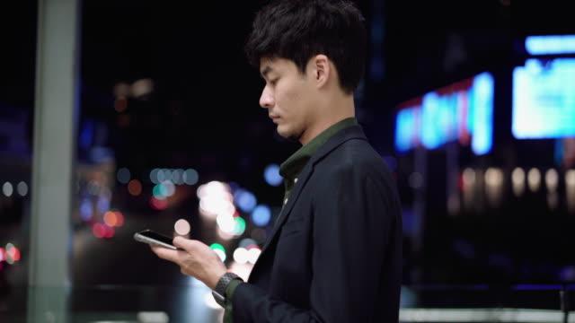 stockvideo's en b-roll-footage met jonge aziatische mens die slimme telefoon bij nachtstraat gebruikt - ingesproken bericht