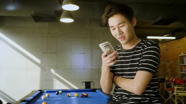 Young Asian man using smart phone next to pool table at co-working space or modern office