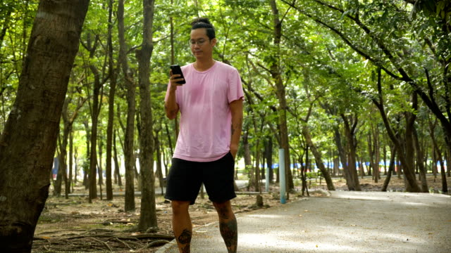 junge asiatische mann mit smartphone am stadtpark. - nur junge männer stock-videos und b-roll-filmmaterial