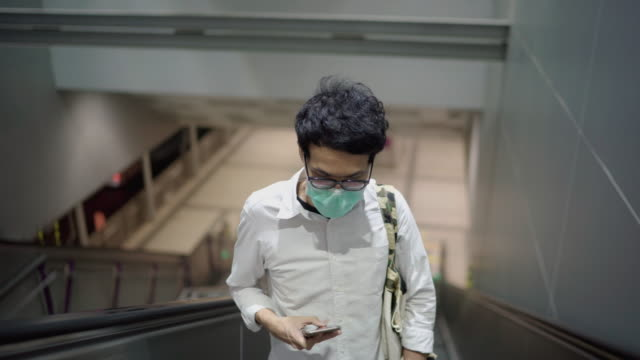 vídeos de stock e filmes b-roll de young asian man using smartphone on escalator - ausência