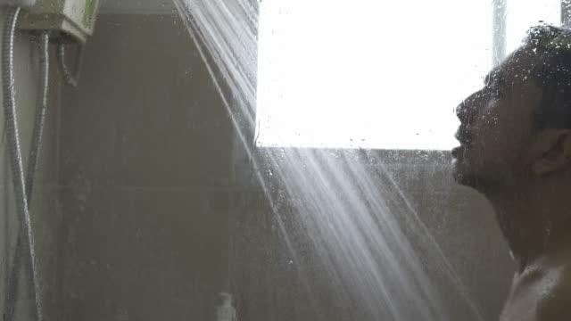 vidéos et rushes de jeune homme asiatique lavant et prenant une douche avec le bain de douche dans la salle de bains - prendre un bain