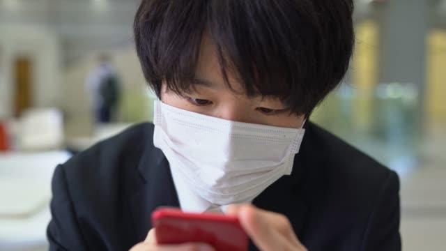 フェイスマスクのテキストメッセージを身に着けている若いアジア人男性 - テキストメッセージ点の映像素材/bロール