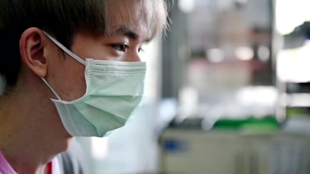 young asian man wearing medical face mask with coughing - asian man coughing stock videos & royalty-free footage