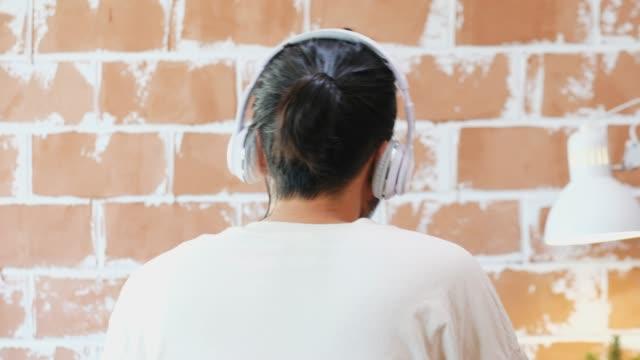 stockvideo's en b-roll-footage met jonge aziatische man met een koptelefoon notering aan muziek met ontspannende emotie, mensen en technologie, generation z levensstijl - generation z