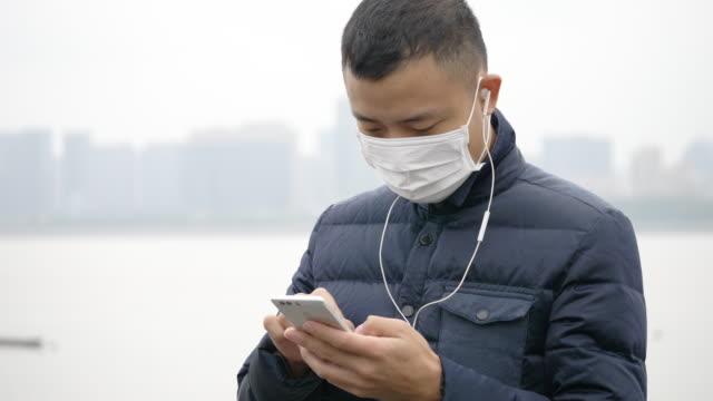vidéos et rushes de jeune homme asiatique avec masque à l'aide de téléphone portable - pollution