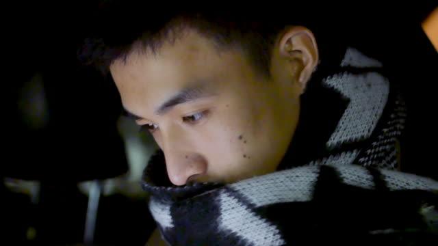 junge asiatische mann mit handy im auto - auto innenansicht stock-videos und b-roll-filmmaterial