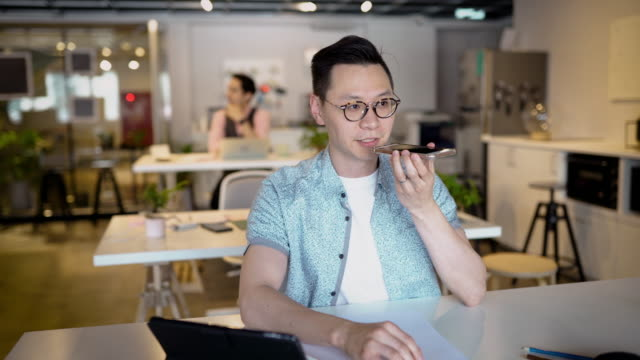 young asian man working in office - voice stock videos & royalty-free footage