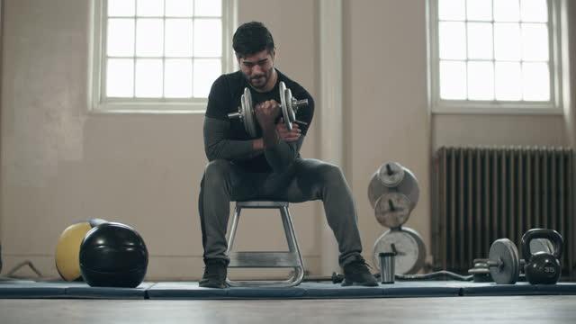 vídeos de stock, filmes e b-roll de young asian man working out in his home gym - peso livre equipamento para exercícios