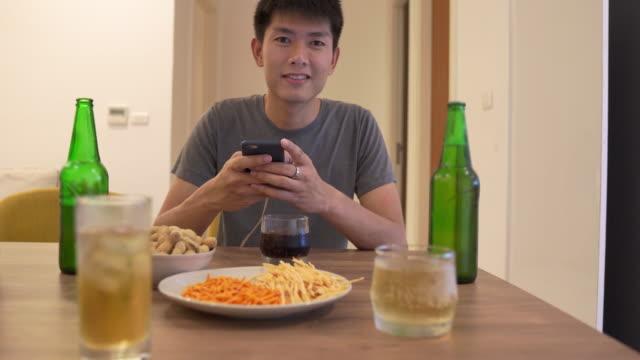 若いアジアの男性が飲んで、自宅でディナーパーティーを持っているスマートで、彼の休暇でリラックス - 飲み物点の映像素材/bロール