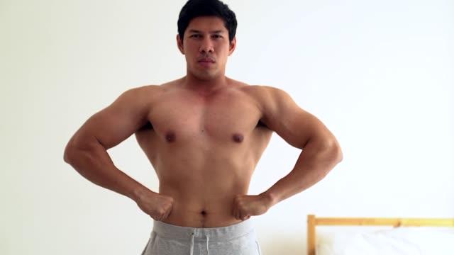 vídeos de stock, filmes e b-roll de tronco de desportivo de jovens asiáticos mostra seu bíceps no quarto dele. - braço