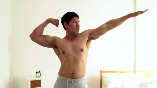 young asian men sporty torso shows his biceps in his room. - torso stock videos & royalty-free footage