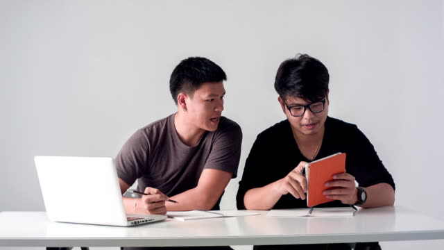 HD DOLLY : Young asian men using laptop computer and digital tablet