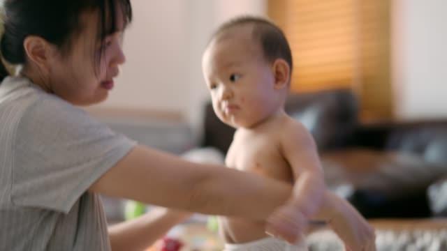 vídeos y material grabado en eventos de stock de joven asiática mamá vestirse de su bebé niño (6-11 meses) - cambiar pañal