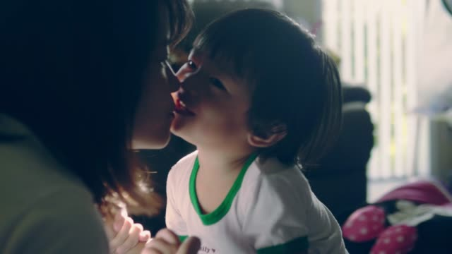 young asian mother and baby kissing on sofa. - asian and indian ethnicities stock videos & royalty-free footage