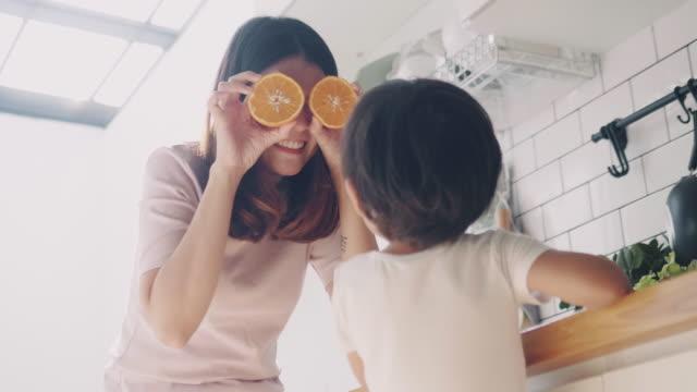vídeos de stock, filmes e b-roll de matriz e filho asiáticos novos que cozinham junto na cozinha home. - fruta