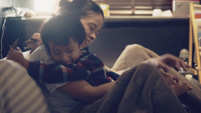 young asian mother and son cuddling and big hugging at home. - bedtime stock videos & royalty-free footage