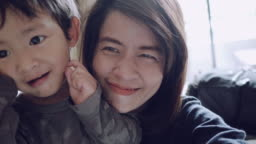 POV : Young asian mother and son taking self portrait.