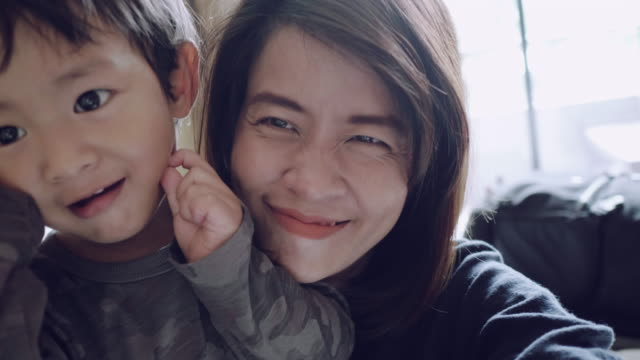 pov : young asian mother and son taking self portrait. - video stock videos & royalty-free footage
