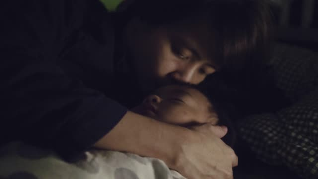 Young Asian Mother Cuddling Her Son At Home.