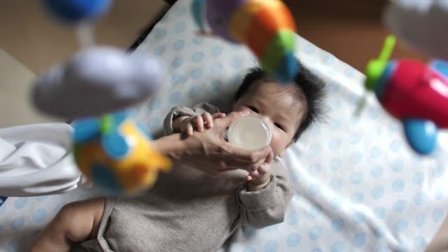 vidéos et rushes de jeune mère asiatique alimentant bébé garçon de bouteille dans la chambre à coucher à la maison - peuples d'asie et du sous continent indien