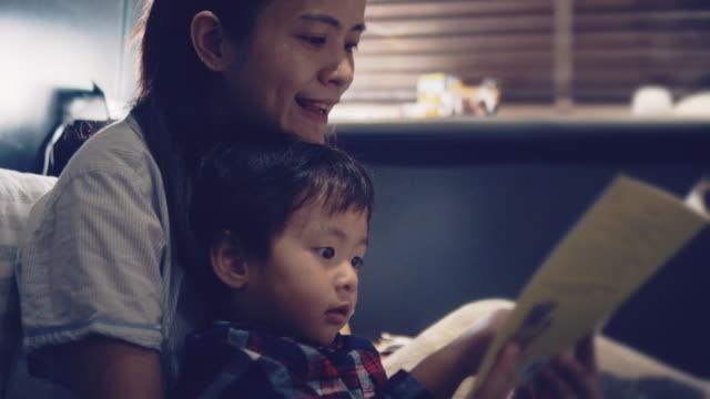 stockvideo's en b-roll-footage met jonge aziatische moeder het lezen van haar zoon een verhaal voor het slapen gaan - prentenboek