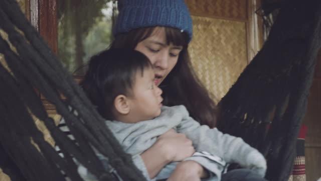stockvideo's en b-roll-footage met jonge aziatische moeder zitten en zoon houden op de schommel thuis - schommelen schommelstoel