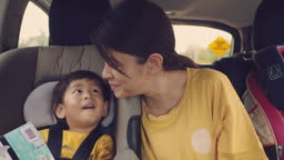 Young asian mother with baby boy traveling by car.