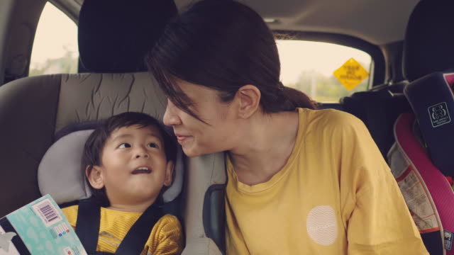 young asian mother with baby boy traveling by car. - car interior stock videos & royalty-free footage