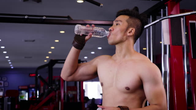 young asian muscular man drinking water from bottle at gym taking a break after workout - solo uomini giovani video stock e b–roll