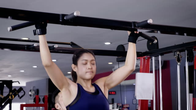 young asian muscular woman exercising doing pull ups on bar in the gym, lifestyle sport and bodybuilding concept - chin ups stock videos and b-roll footage