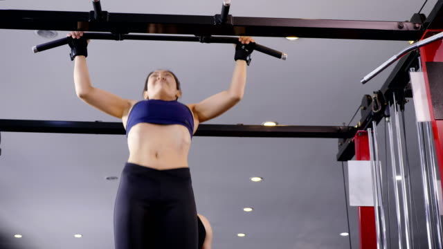 Young Asian muscular woman exercising doing pull ups on bar in the gym, lifestyle sport and bodybuilding concept