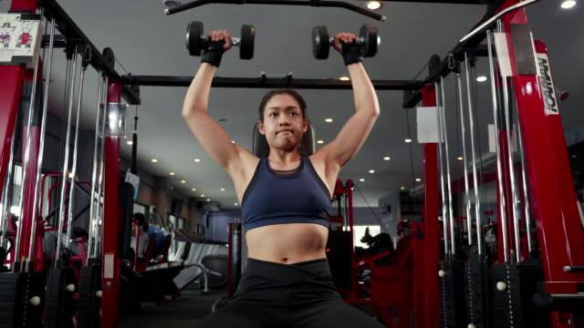 unga asiatiska muskulös kvinna utövar hantel axeln press i gymmet, sport och bodybuilding livsstilskoncept - människoarm bildbanksvideor och videomaterial från bakom kulisserna