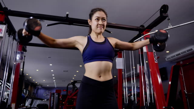 young asian muscular woman exercising dumbbell shoulder raise in the gym, lifestyle sport and bodybuilding concept - arms raised stock videos & royalty-free footage